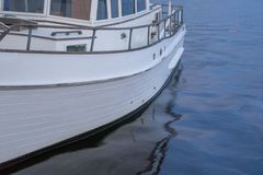 Cruising Vessel with Smooth Reflection. North Carolina - a wooden trawler power boat reflects in the smooth water royalty free stock image