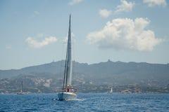 Cruising yacht in a blue waters of Mediterranean sea, Sardinia island. Royalty Free Stock Photo