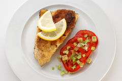 Crumbed carp fillet on tomato on a plate Stock Photo