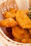 Crumbed chicken nuggets in a basket. Crispy fried crumbed chicken nuggets in a wicker basket served as a finger food or appetizer with a creamy dip in a bowl royalty free stock image