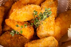 Crumbed chicken nuggets in a basket. Crispy fried crumbed chicken nuggets in a wicker basket served as a finger food or appetizer with a creamy dip in a bowl stock photography
