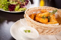 Crumbed chicken nuggets in a basket. Crispy fried crumbed chicken nuggets in a wicker basket served as a finger food or appetizer with a creamy dip in a bowl stock photos