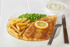 Crumbed Fiah and Chips. Crumbed Fish with Chips, Peas and Tartare Sauce stock photo