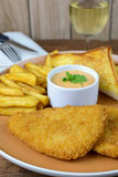 Crumbed fish and chips with glass of wine Royalty Free Stock Images
