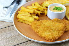 Crumbed fish and chips. On wooden table stock photos