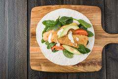 Crumbed fish fillet burrito with avocado and tomato Stock Photo