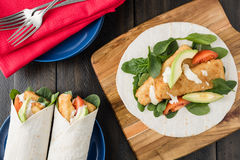 Crumbed fish fillet burrito with avocado and tomato Royalty Free Stock Photo