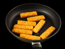 Crumbed fish fingers in fry pan Royalty Free Stock Images