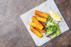 Crumbed fish fingers. Tasty savory snack of crumbed fish fingers sticks served on paper with lemon over dark stone background, top view with copy space stock images