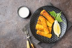 Crumbed fish fingers. Tasty savory snack of crumbed fish fingers sticks served on a plate with lemon over dark stone background, top view with copy space royalty free stock photography