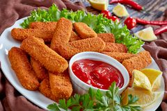 Crumbed fish sticks served with ketchup. Crumbed fish sticks served with lemon, lettuce leaves and tomato sauce on a white plate on a wooen rustic table royalty free stock photography