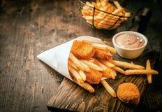 Crumbed frió pepitas de los pescados con las patatas fritas Imagen de archivo