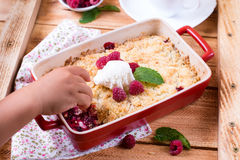 Crumble with berries and hand. On a wooden background Stock Image