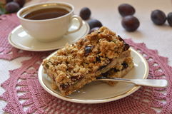 Crumble cake with plums.  Homemade crumble cake with plums, oatmeal and cup of coffee Stock Photography