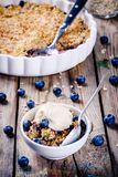 Crumble caseiro do mirtilo da farinha de aveia com gelado Imagens de Stock Royalty Free