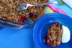 Crumble. Peach and raspberry crumble, served with cream. Selective focus Royalty Free Stock Images