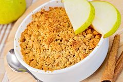Crumble with pears in bowl on linen tablecloth Royalty Free Stock Photos