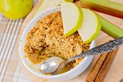 Crumble with pears and rhubarb in bowl on cloth Stock Photos