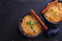 Crumble with plums and cinnamon. On a black background royalty free stock photos