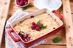 Crumble with raspberries. On a wooden background Royalty Free Stock Images