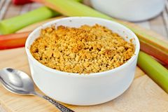 Crumble with rhubarb in bowl on tablecloth Stock Images