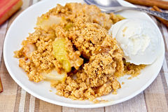 Crumble with rhubarb in dish on linen tablecloth Royalty Free Stock Image