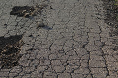 Crumbled asphalt. With cracks and potholes Stock Photos