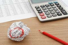 Crumbled document on wooden table with calculator and red pencil. Selective focus Stock Image