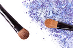 Crumbled eyeshadow with brush. Closeup on white Stock Images