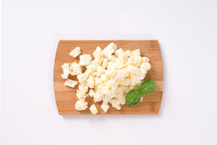 Crumbled feta cheese. Pile of crumbled feta cheese on wooden cutting board Stock Photography