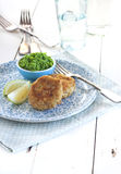 Crumbled fish patties. Fish patties with peas purée and lemon on blue plate and rustic wooden table stock photo