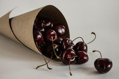Crumbled berries of ripe cherries in a paper rolled bag close-up royalty free stock photos