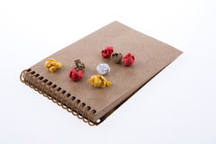 Crumbled paper on a notebook. Colorful crumbled paper on a notebook on a white background Stock Images