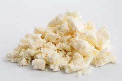 Crumbled white feta cheese  on white. Crumbled white feta cheese  on white surface Stock Photo