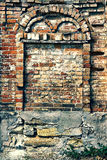 Crumbling brick wall with arch Stock Photography