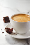 Crumbling chocolate brownie on latte coffee cup and saucer Stock Photo