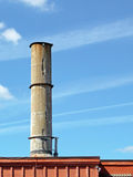 Crumbling concrete smokestack against a blue sky Royalty Free Stock Photo