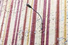 The crumbling flaking old paintwork on an old and aging wall of tenement house with street lamp.  The painting begins to fade and. Loose color royalty free stock photos