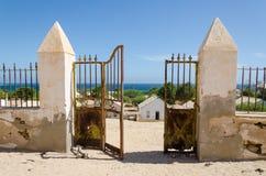 Crumbling metal gate of colonial stone wall overlooking beautiful ocean in Angola. Crumbling metal gate of colonial stone wall overlooking beautiful ocean in Royalty Free Stock Images