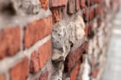 A crumbling old red brick wall background texture in shallow depth of field. stone wall selective focus.  stock images