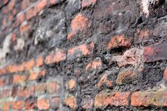 A crumbling old red brick wall background texture in shallow depth of field. stone wall selective focus.  stock photos