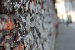 A crumbling old red brick wall background texture in shallow depth of field. stone wall selective focus.  royalty free stock photos
