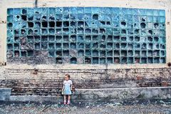 Crumbling wall. broken glass, little defenseless girl Royalty Free Stock Photography