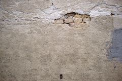 Crumbling wall. The crumbling plaster layers of an old wall with repair points Stock Photography