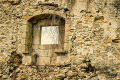Crumbling wall. Crumbling exterior wall with window of an old stone house Stock Photo