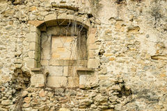 Crumbling wall. Crumbling exterior wall with window of an old stone house Stock Image