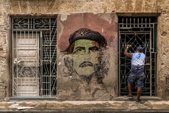Crumbling wall painted with face of Che Guevara in Cuba. Man facing barred door next to Che Guevara`s face on crumbling Havana street, conveys: trapped, irony Stock Photography
