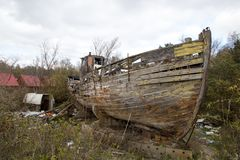 Crumbling wooden boat on the shore. Crumbling wooden old retro vintage boat on the shore, around the boat a lot of garbage Royalty Free Stock Photography