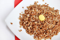Crumbly buckwheat with butter on white Stock Photos