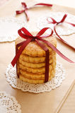 Crumbly cookies tied with ribbon and bow on light brown background Royalty Free Stock Photo
